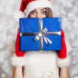 Cute teenage girl with Santa hat holding blue gift box against snow background — Stock Photo