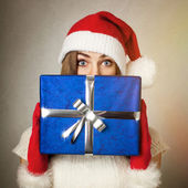 Cute teenage girl with Santa hat holding blue gift box — Stock Photo
