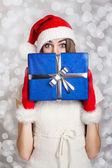 Ragazza adolescente carina con cappello santa holding scatola regalo blu su sfondo di neve — Foto Stock