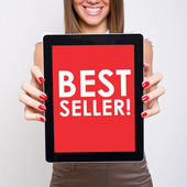 Woman showing tablet computer that states best seller — Stockfoto