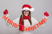 Happy young Santa woman holding Merry Christmas text decoration — Foto Stock