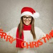 Beautiful young Santa girl with Merry Christmas text decoration — Foto Stock