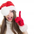 Surprised girl with Santa Claus beanie and gloves pointing up — Stock Photo