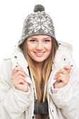 Beautiful teenage girl wearing winter jacket and knitted beanie hat posing — Stock Photo