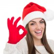 Excited young woman wearing Santa Claus hat gesturing ok — Stock Photo