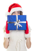 Surprised teenage girl wearing Santa beanie holding big giftbox — Stock Photo