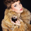 Elegant lady with red wine wearing brown fur coat — Stock Photo