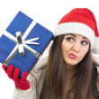 Young Santa woman wondering what is in the blue gift box — Stock Photo
