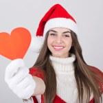 Cute teenage Santa girl showing red heart — Stock Photo