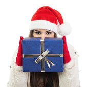 Young woman with Santa hat holding big blue gift box — Stock Photo