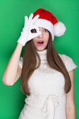 Cute teenage girl with Santa hat looking on one eye — Stock Photo