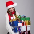 Happy young woman laughing carrying many presents — Stock Photo