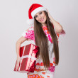 Fashionable young woman with Santa hat holding big gift box — Stock Photo #37334453