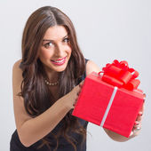 Happy young woman showing big red gift box — Stock Photo