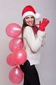 Happy Christmas girl holding balloons waving — Stock Photo