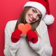 Cute young woman with Santa hat showing red paper heart — Stock Photo