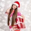 Cute young modern Santwomwith long hair and gift box — Stock Photo #37650421