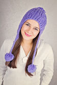 Happy young woman with fashionable purple beanie hat — Stock Photo