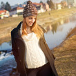 Pretty young pregnant woman taking a walk by the river — Stockfoto