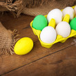 Colorful Easter eggs in yellow carton with jute decoration — Stock Photo