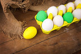 Colorful Easter eggs in yellow carton with jute decoration — Stock fotografie
