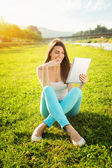 Happy teenage girl with tablet in nature — Stock Photo