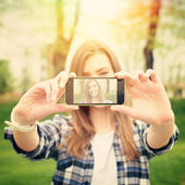 Beautiful young woman taking a selfie photo with phone — Stock Photo