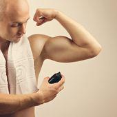 Fit young man applying antiperspirant spray deodorant — Stock Photo