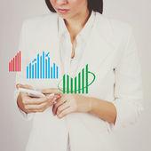 Businesswoman checking charts on smart phone — Stok fotoğraf