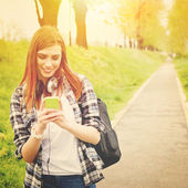 Teenage student girl with smart phone texting — Stock Photo