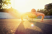 Young fit shirtless man doing push-ups outdoors — Stock Photo