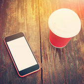 Smart phone and takeaway coffee on wooden surface outdoors — Stock Photo