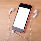 Smartphone mit Kopfhörer auf hölzernen Oberflächen-Nachbildung — Stockfoto