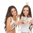 Two happy fashionable young women showing thumbs up wearing colorful jewelry — Stock Photo