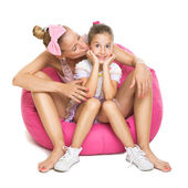 Young mother and daughter sitting on pink bean bag — Stock Photo