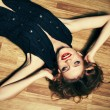 Fashionable young woman lying on wooden floor and laughing. stud — Stock Photo