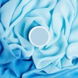 Beauty cream box over turquoise vapory and wavy cloth background — Stock Photo #14626173