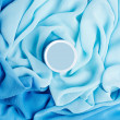 Beauty cream box over turquoise vapory and wavy cloth background - Stock Photo