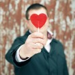 Hand of groom holding red sweet heart. outdoor shot — Stock Photo