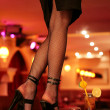 Stock Photo: Sexy legs of a waitress standing on the bar. indoor shot