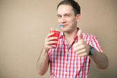 Ragazzo felice azzurri hipster bere e mostrando pollice sopra fondo in legno — Foto Stock