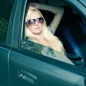 Magnificent blonde girl with sunglasses sitting in the blue colo — Stock Photo