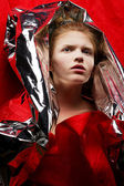 Arty portrait of a fashionable red-haired model in red with silv — Stock Photo