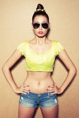 Portrait of a fashionable model in sunglasses over wooden backgr — Foto de Stock