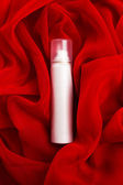 Beauty spray (aerosol) over red vapory and wavy cloth background — Stockfoto