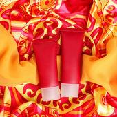 Two vinous plastic cream tubes over motley cloth background. stu — Stock Photo