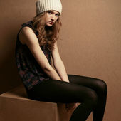 Fashionable model with curly red hair and beige hat sitting on a — Stock Photo