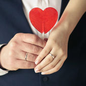Loving hands holding sweet red heart — Stock Photo