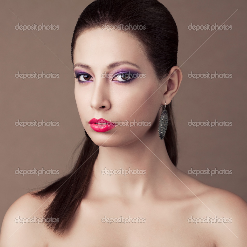 Fashionable model with brown hair, vintage earrings and great make-up over the wooden background. studio shot  Stock Photo #14883735