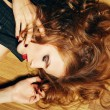 Fashionable young woman with ginger hair lying on wooden floor a — Stock Photo